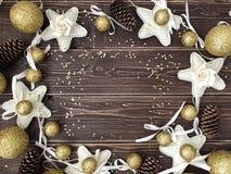 与金黄球、星和杉木锥体的木背景 库存图片