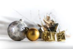 与金黄礼物的两个圣诞节球 免版税图库摄影