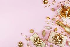 与金黄礼物的圣诞节背景或当前箱子、香槟和假日装饰在桃红色淡色台式视图 平的位置 免版税图库摄影
