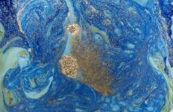 与金黄衣服饰物之小金属片的使有大理石花纹的蓝色抽象背景 液体大理石墨水样式 免版税库存照片
