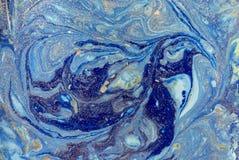 与金黄衣服饰物之小金属片的使有大理石花纹的蓝色抽象背景 液体大理石墨水样式 库存照片