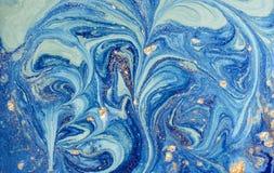 与金黄衣服饰物之小金属片的使有大理石花纹的蓝色抽象背景 液体大理石墨水样式 图库摄影