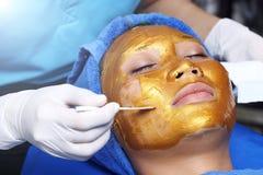 与金黄面具奶油按摩的防皱脸面护理 库存图片