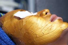 与金黄面具奶油按摩的防皱脸面护理 免版税库存照片