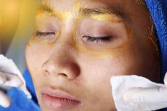 与金黄面具奶油按摩的防皱脸面护理 免版税库存图片