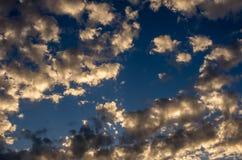 与金黄云彩的剧烈的日落天空在雷暴以后 免版税图库摄影