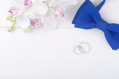 与金黄圆环的婚礼背景在白色木桌上 免版税图库摄影