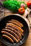 与金黄外壳的可口油煎的香肠在铁熔铸了平底锅,新鲜的荷兰芹蕃茄 免版税库存照片
