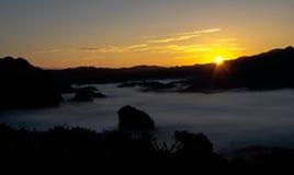 与金黄天空和早晨薄雾的日出风景在北泰国 免版税库存照片