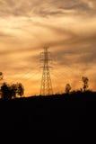 与金黄天空的高压杆 库存图片