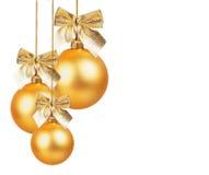 与金黄弓的三个金子圣诞节球 免版税库存照片