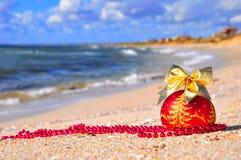 与金黄弓的红色圣诞节球在沙子 免版税图库摄影