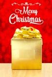 与金黄当前箱子的圣诞快乐在红色bok的木桌上 库存图片