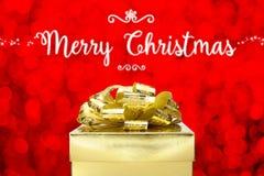 与金黄当前箱子的圣诞快乐在红色bokeh光backg 免版税库存图片
