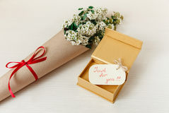 与金黄当前箱子的特别愿望卡片有花束白色小花的在布朗工艺纸 白色木纹理背景 免版税库存图片