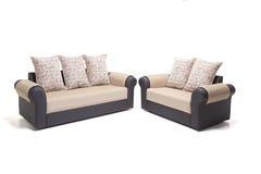 与金黄盖子和坐垫的黑皮革沙发集合在它有白色背景 库存照片