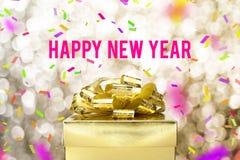 与金黄礼物盒的新年好词有丝带和colorfu的 库存照片