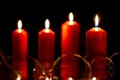 与金黄蛇纹石和反射的四个红色蜡烛 免版税库存照片
