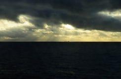 与金黄阳光光芒的黑暗的风雨如磐的天空,货船 免版税库存图片