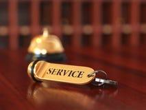 与金黄keychain服务概念的房间钥匙在木后面 图库摄影