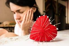 与针和年轻人生气妇女,选择聚焦的红色心脏 免版税库存图片