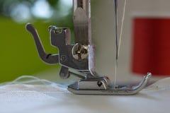 与针的缝纫机` s脚缝合ecru颜色织品 关闭-  库存照片