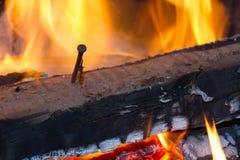 与钉子的灼烧的木头 库存图片
