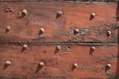 与钉子的老木,切削的门在阳光下构造背景 库存图片