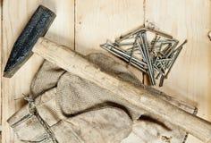 与钉子的葡萄酒锤子在木背景 免版税库存照片