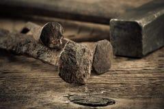 与钉子的葡萄酒锤子在木背景 免版税库存图片