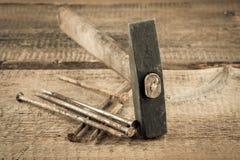 与钉子的葡萄酒锤子在木背景 库存图片