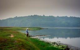 与钓鱼勾子的人钓鱼在从Ithikkunnu夺取的早晨,Padapuzha 免版税库存照片