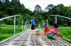 与钓鱼在竹桥梁的孩子的泰国妇女画象在Ba 库存照片