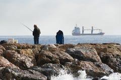 与钓鱼竿的一个渔夫身分在他的手上,他继续下去  免版税库存照片