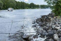 与钓鱼竿的夏天风景在湖背景,在岸对面,早晨,游艇,与石头的海滩 季节 免版税库存图片