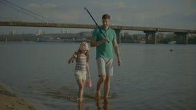 与钓鱼竿的无忧无虑的家庭走在水中的 股票视频