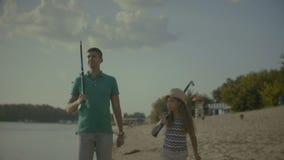 与钓鱼竿的聊天的家庭走在海滩的 股票录像