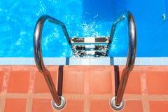 与钢台阶的游泳池 免版税库存图片