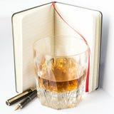 与钢笔的威士忌酒玻璃和笔记、创造性和lifestyl 库存照片