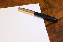 与钢笔的白皮书在木桌上 免版税库存图片