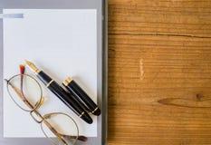 与钢笔的笔记本纸 免版税库存照片