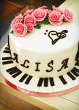 与钢琴钥匙、高音谱号和玫瑰的乳脂状的蛋糕 免版税图库摄影