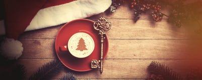 与钥匙的热奶咖啡在桌上 库存图片