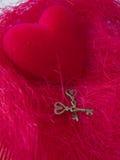 与钥匙的红色心脏在红色背景 免版税库存照片