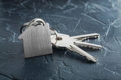 与钥匙,与房子标志,石背景的keychain的庄园概念 免版税库存照片