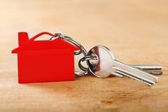 与钥匙,红色keychain,房子标志木背景的庄园概念 库存照片