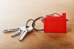 与钥匙,红色keychain,房子标志木背景的庄园概念 免版税库存图片
