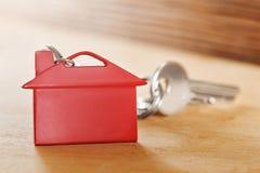 与钥匙,红色keychain,房子标志木背景的庄园概念 图库摄影