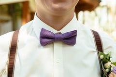 与钮扣眼上插的花的新郎紫色颜色蝶形领结 库存照片