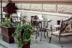 与铁伪造的腿和玻璃台式的一张桌 免版税库存照片
